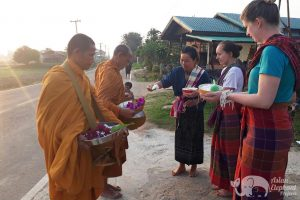 giving alms to monks while volunteering at ethical elephant sanctuary near Surin in Thailand