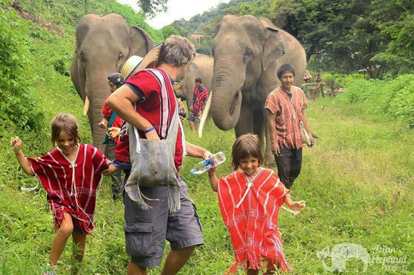 Children walking happily with elephants at ethical elephant sanctuary near Chiang Mai in Thailand